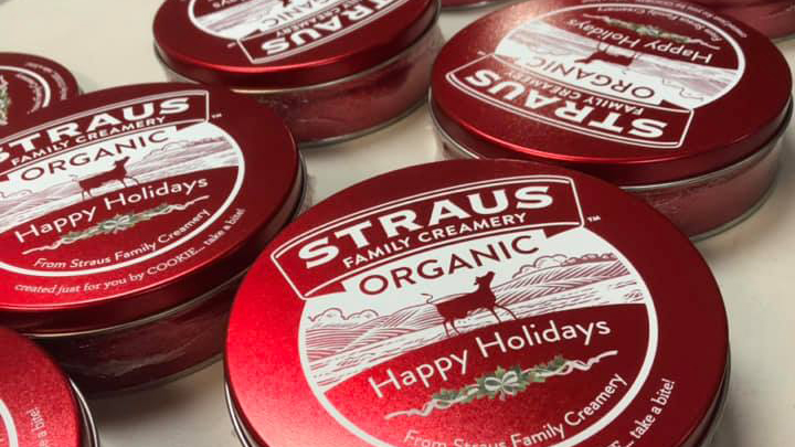 red circular cookie tins with straus family creamery logo and holiday message printed on lid