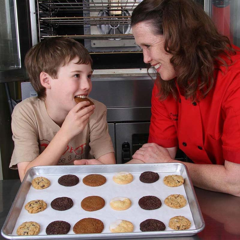 owner of cookie take a bite and her son enjoying a fresh baked cookie