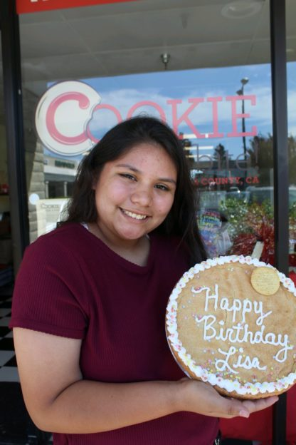 woman holding up large decorated birthday cookie cake