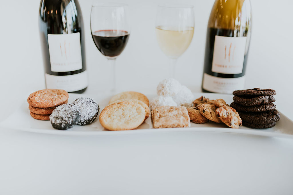 A plate of gourmet handmade cookies in front of two bottles of wine for a Valentine's Day pairing
