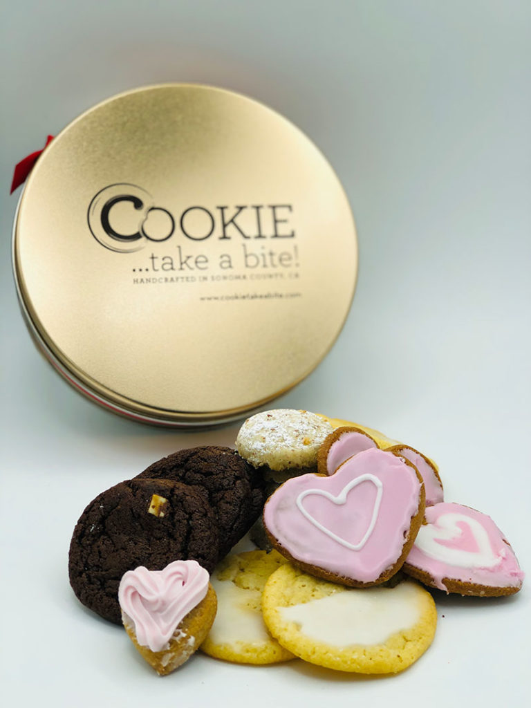 Cookie...take a bite! Deluxe Mother's Day Tin with a variety of cookies in front including pink heart-shaped cookies.