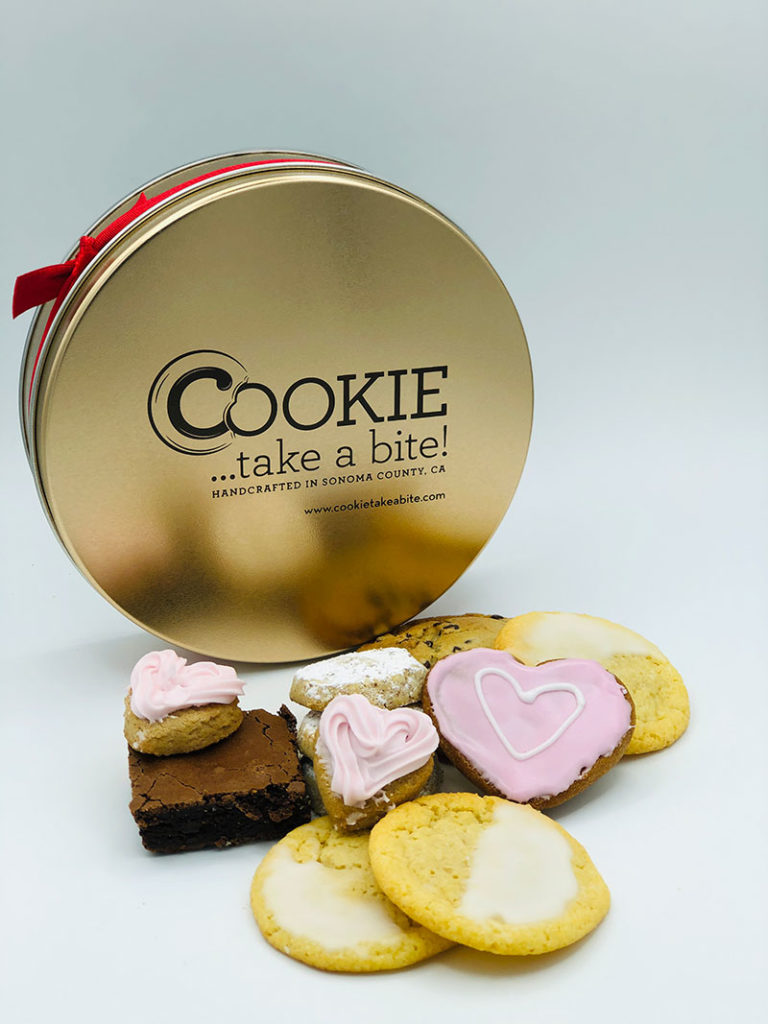 Cookie...take a bite! Premium Mother's Day Tin with a variety of cookies in front including pink heart-shaped cookies.